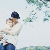 木陰で赤ちゃんを抱く母親