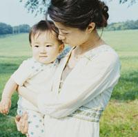 草原で赤ちゃんを抱く母親