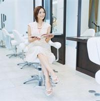 美容室で雑誌を読む20代日本人女性