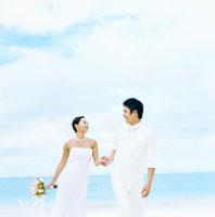 浜辺で花嫁の手を持って歩く日本人の花婿