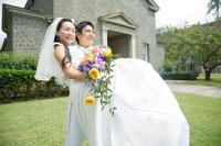 教会の前で花嫁を抱きかかえる花婿