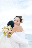 浜辺で花婿に抱きつく日本人の花嫁