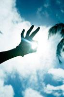 太陽にかざした手のシルエット