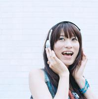 街中で音楽を聴く20代日本人女性