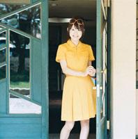 ドアを開けて微笑む20代日本人女性