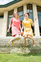 屋外でジャンプをする20代日本人女性2人