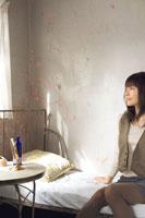 ベッドルームから外を眺める20代日本人女性
