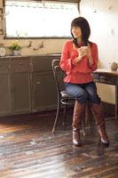 キッチンで椅子に座りお茶を飲む20代日本人女性