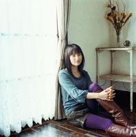 窓辺に座ってくつろぐ20代日本人女性