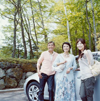 車から降りて新緑を眺めるシニア夫婦と娘