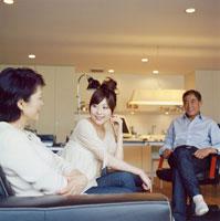 リビングで寛ぐ日本人シニア夫婦と娘