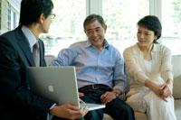 ビジネスマンと商談する日本人シニア夫婦