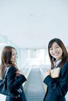 エスカレーターで笑う日本人女性新入社員2人