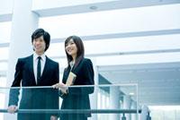 オフィスで遠くを眺める日本人新入社員の男女