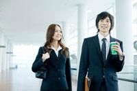 オフィス内を歩く日本人新入社員の男女