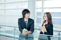 オフィスで会話をする日本人新入社員の男女