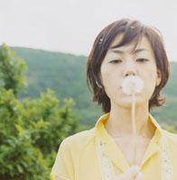 たんぽぽの綿毛を吹く女性の顔 30010000124| 写真素材・ストックフォト・画像・イラスト素材|アマナイメージズ