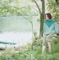 湖の上のボートと木の枝に座る女性
