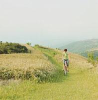 野原を自転車で走る女性
