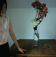 机の上の生け花と女性