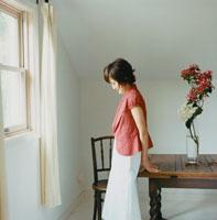 机にもたれる女性 30010000181| 写真素材・ストックフォト・画像・イラスト素材|アマナイメージズ