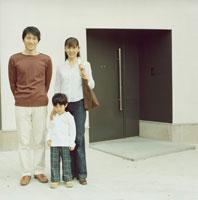 一軒屋の前に立つ日本人家族