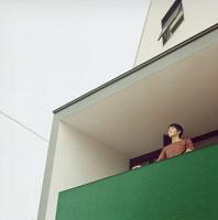 ベランダから外を見る日本人男性