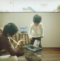 虫篭から虫を出す男の子と父親 30010000242| 写真素材・ストックフォト・画像・イラスト素材|アマナイメージズ
