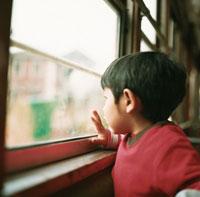 電車の窓から外を眺める男の子