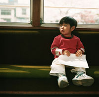 電車の座席に座る男の子