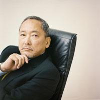 椅子に腰掛けるスーツ姿の日本人シニア男性
