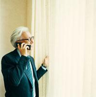 携帯電話で話す日本人のシニア男性