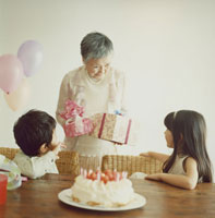 祖母にプレゼントを渡す日本人の男女の孫