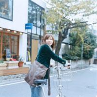 自転車を押して振り向く日本人女性