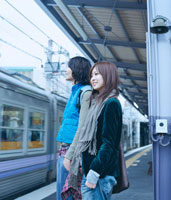 ホームで電車を待つ20代日本人カップル
