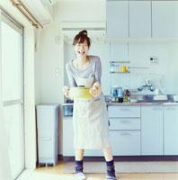 キッチンで料理をしながら笑う20代日本人女性