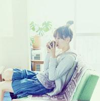 室内でコーヒーを飲む20代日本人女性