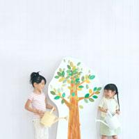 イラストの木に水遣りをする日本人の女の子
