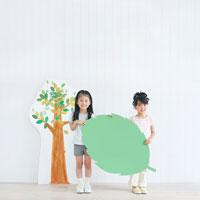 イラストの木の前でメッセージボードを持つ女の子達