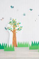 イラストの木の前を飛び交うクラフトの蝶々