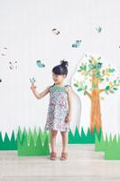 イラストの木の前でクラフトの蝶々と遊ぶ女の子