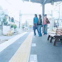 ホームで電車を待つ20代日本人のグループ