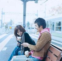 ホームのベンチでメールを見る20代日本人カップル