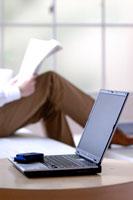 ソファで新聞を読むビジネスマンとテーブルのパソコン