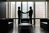 応接室で握手をする2人のビジネスマン