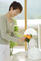 花瓶に花を生けるシニア女性