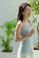 室内でペットボトルを手にする20代日本人女性 30015000926| 写真素材・ストックフォト・画像・イラスト素材|アマナイメージズ