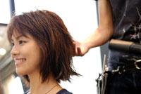 美容室で髪をセットしてもらう20代日本人女性