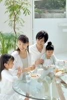 テーブルで食事をする日本人の家族