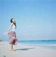 浜辺で風を感じている日本人の若い女性